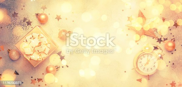 istock Christmas or New Year composition, frame, gray background with gold Christmas decorations, stars, snowflakes, balls, alarm clock, gift box, banner, top view 1176200371
