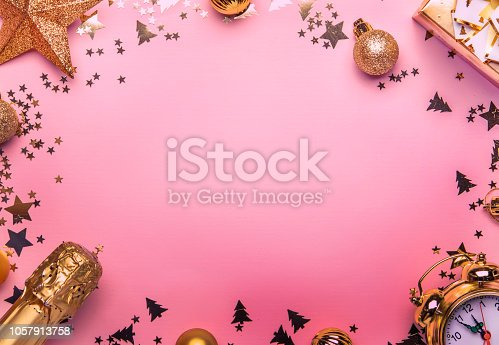 istock Christmas or New Year composition, frame, pink background with gold Christmas decorations, stars, snowflakes 1057913758