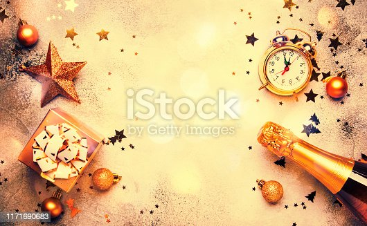 istock Christmas or New Year composition, frame, pink background with gold Christmas decorations, stars, snowflakes, balls, alarm clock, gift box and bottle of champagne, top view 1171690683