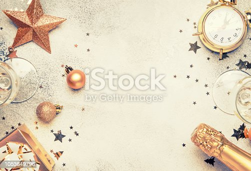 Christmas or New Year composition, gray background with gold Christmas decorations, stars, snowflakes, balls, alarm clock, gift box, top view