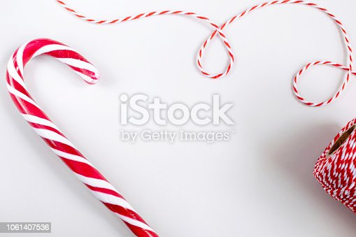Christmas or New Year concept - Candy canes and twisted red and white cord. White background, top view, copy space.