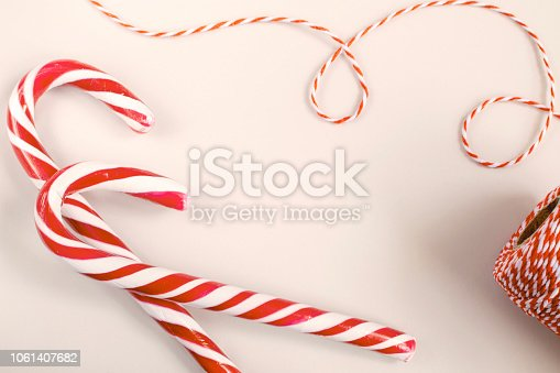 Christmas or New Year concept - Candy canes and twisted red and white cord. White background, top view, copy space, toned