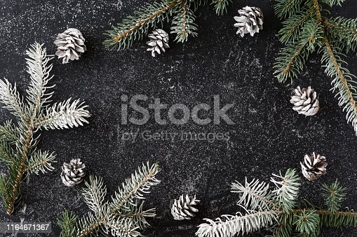 Christmas or New Year decoration background of fur-tree branches and snow on black grunge background with copy space