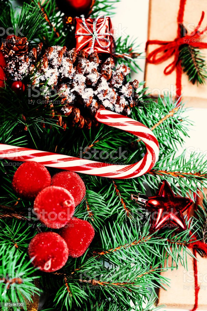 7fb38ce60f0d Christmas or New Year decorations background with pine cones, fir branches,  gift boxes, red berries and candy isolated on white background - Stock  image .