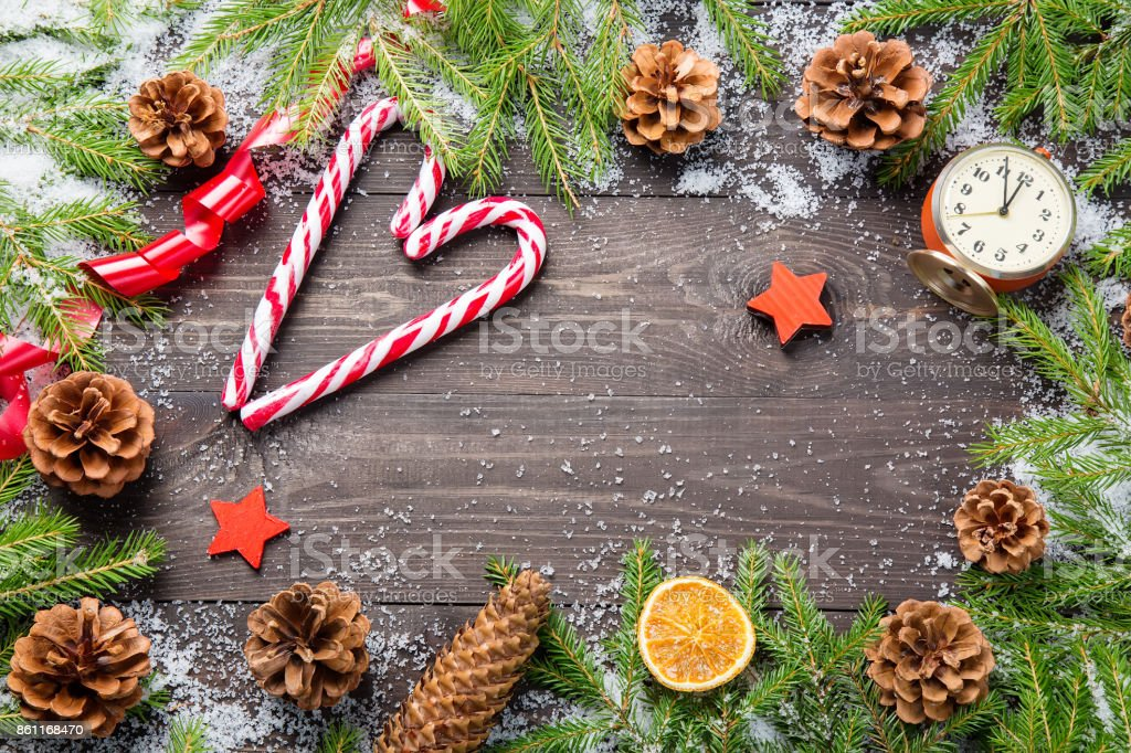 Christmas or new year frame for your project with copy space. Christmas fir trees in snow with cones, candy canes, vintage clock, decorative stars and red ribbono n a dark wooden board. stock photo