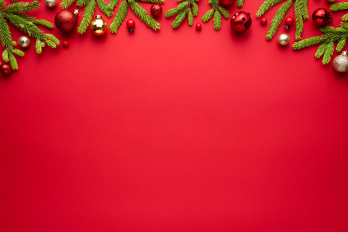 Christmas or New Year red background with fir decor. Blank for advertising text with copy space. Top view, flat lay