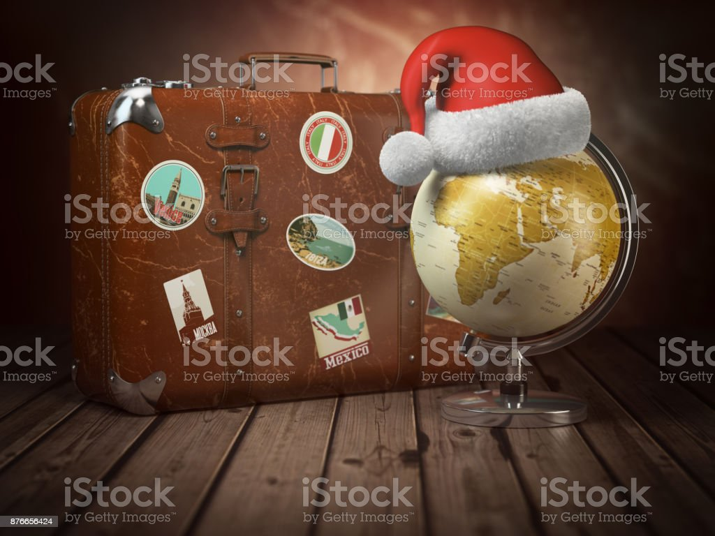Christmas or new year travel concept. Old suitcase with globe nad santa hat on wood  background. stock photo