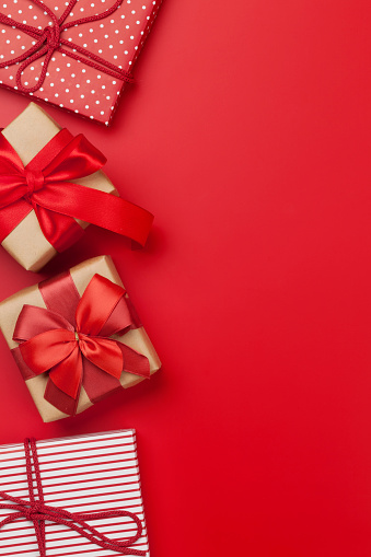 Christmas or Valentine's day gift boxes on red background. Top view with copy space. Flat lay