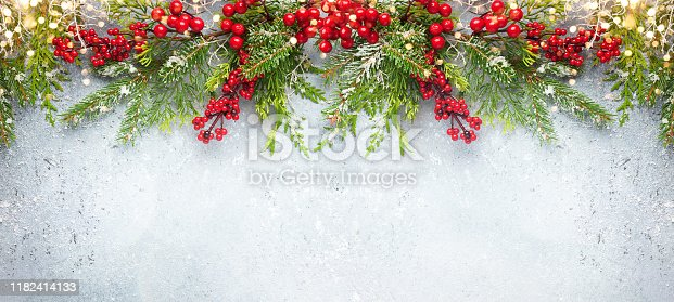 istock Christmas or winter background with a border of evergreen branches and red berries 1182414133