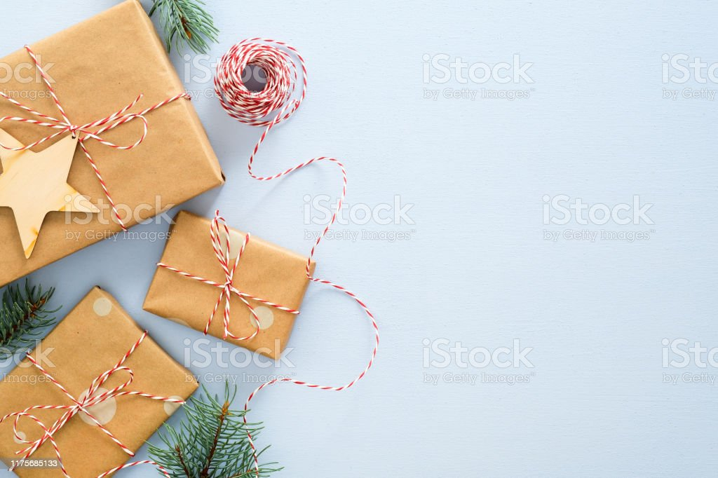 Christmas or winter composition. Frame made of gifts box wrapped kraft paper, twine rope, wooded Xmas decorations, fir tree branches on pastel blue background. Christmas, winter, new year concept - Стоковые фото Без людей роялти-фри