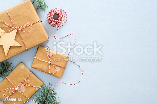 Christmas or winter composition. Frame made of gifts box wrapped kraft paper, twine rope, wooded Xmas decorations, fir tree branches on pastel blue background. Christmas, winter, new year concept
