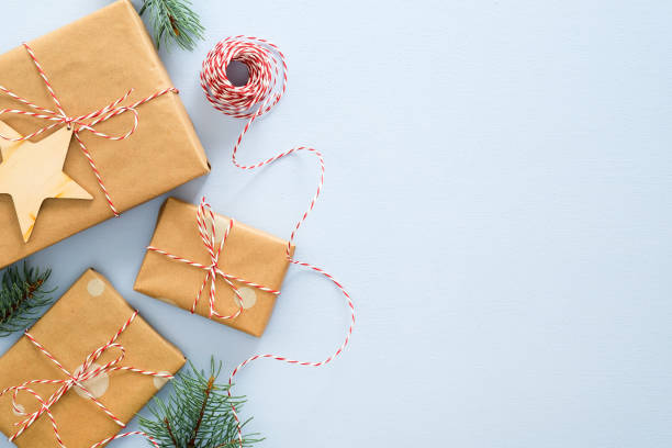 kompozycja świąteczna lub zimowa. rama wykonana z pudełka z prezentami owiniętego papierem kraftowym, liną sznurka, zalesionymi dekoracjami xmas, gałęziami jodły na pastelowym niebieskim tle. boże narodzenie, zima, nowy rok koncepcji - gift zdjęcia i obrazy z banku zdjęć