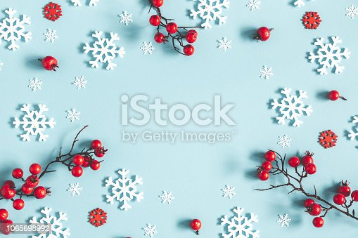 istock Christmas or winter composition. Frame made of snowflakes and red berries on pastel blue background. Christmas, winter, new year concept. Flat lay, top view, copy space 1065698992