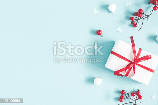 1076063742 istock photo Christmas or winter composition. Gift, snowflakes, white balls and red berries on pastel blue background. Christmas, winter, new year concept. Flat lay, top view, copy space 1074099834