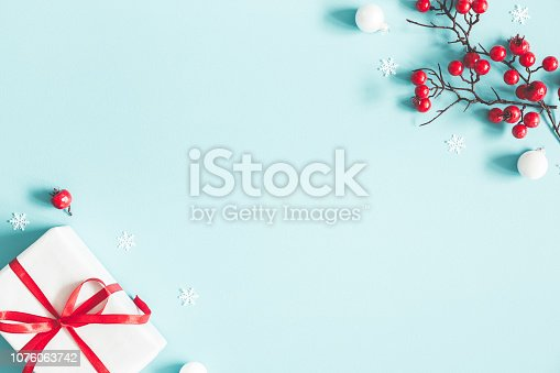 Christmas or winter composition. Gift, snowflakes, white balls and red berries on pastel blue background. Christmas, winter, new year concept. Flat lay, top view, copy space
