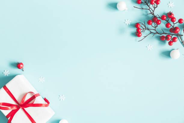 composizione natalizia o invernale. regalo, fiocchi di neve, palline bianche e bacche rosse su sfondo blu pastello. concetto di natale, inverno, capodanno. lay piatto, vista dall'alto, spazio di copia - flat lay foto e immagini stock