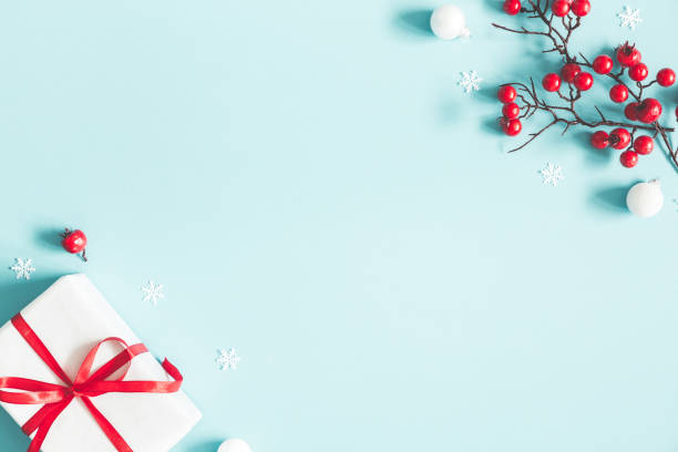 christmas or winter composition. gift, snowflakes, white balls and red berries on pastel blue background. christmas, winter, new year concept. flat lay, top view, copy space - moldura composição imagens e fotografias de stock