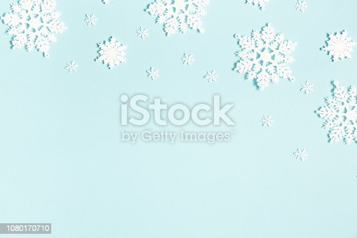 1076063742 istock photo Christmas or winter composition. Pattern made of snowflakes on pastel blue background. Christmas, winter, new year concept. Flat lay, top view, copy space 1080170710