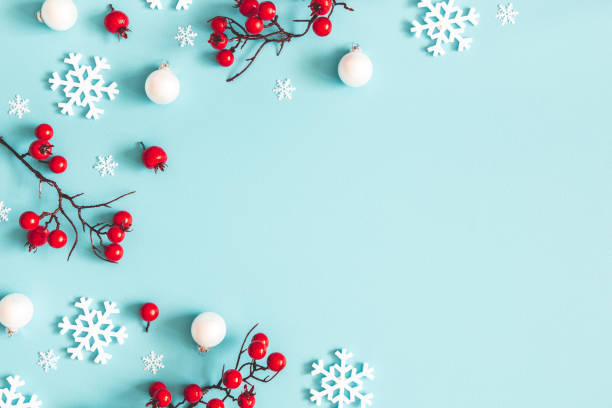 Christmas or winter composition. Snowflakes and red berries on blue background. Christmas, winter, new year concept. Flat lay, top view, copy space stock photo