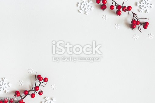 istock Christmas or winter composition. Snowflakes and red berries on gray background. Christmas, winter, new year concept. Flat lay, top view, copy space 1184779713