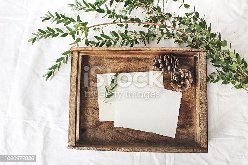 Christmas or winter wedding mock-up scene. Blank cotton paper greeting cards, old wooden tray, pine cones and green Eucalyptus parvifolia branch, white bed linen background. Flat lay, top view.
