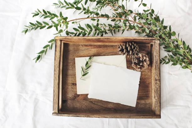 크리스마스 또는 겨울 결혼식 모형 장면. 빈 면 종이 인사말 카드, 오래 된 나무 트레이, 소나무 콘 및 녹색 유 칼 리 나무 2, 250 점. 흰색 침대 린 넨 배경입니다. 평면 위치, 최고 볼 수 있습니다. - 초대장 뉴스 사진 이미지