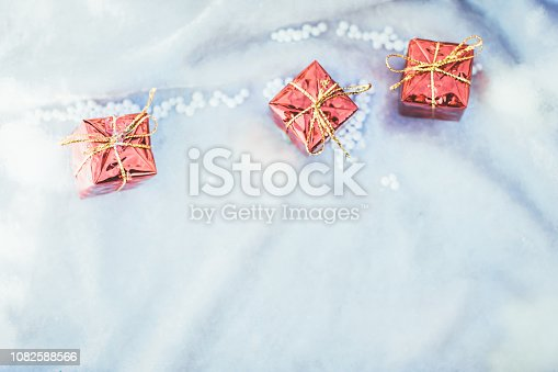 1076063742 istock photo Christmas ornament flat lay  background with gift boxes and snow 1082588566