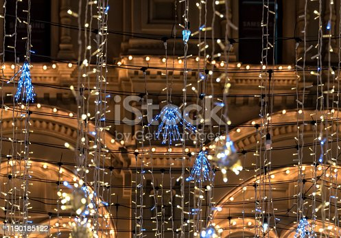 Christmas ornament garlands on the street as background.The picture shows a fragment of Christmas illumination on the old Moscow Nikolskaya Street (Moscow, Russia). Illumination is mounted by city services and represents LED bulbs hanging in the form of rain. In the background is one of the old buildings located on this street.