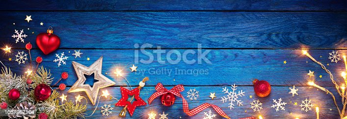 istock Christmas Ornament On Blue Table With String Light 1057967104