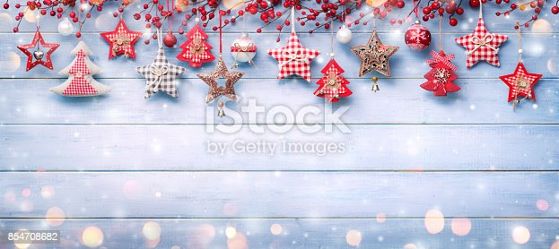 istock Christmas Ornaments And Berries Hanging On Snowy Wooden 854708682