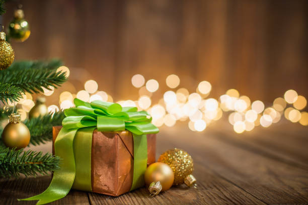 Christmas Ornaments and Gift on Wood Background with defocused lights sparkles stock photo