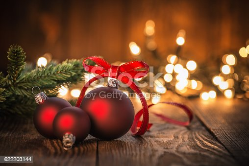 Christmas Ornaments on Wood Background and defocused lights. Spruce Tree branch on the left.