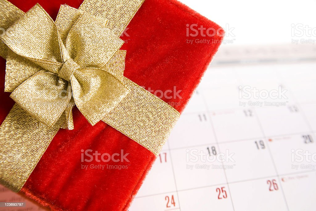 Christmas Package. Red, gold gift on December calendar. stock photo
