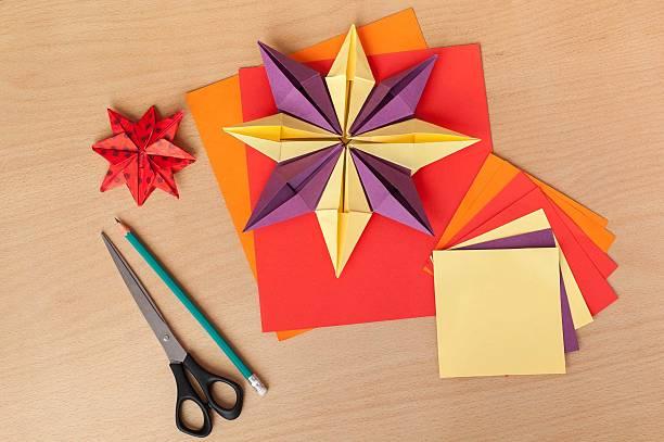 christmas paper stars on a wooden table. - origami anleitungen stock-fotos und bilder