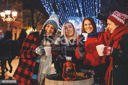 Group of jolly friends cheering with hot drinks on a cold Christmas night.