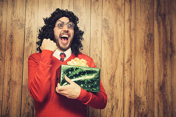 christmas perm guy celebrates a gift - ugly sweater stock photos and pictures