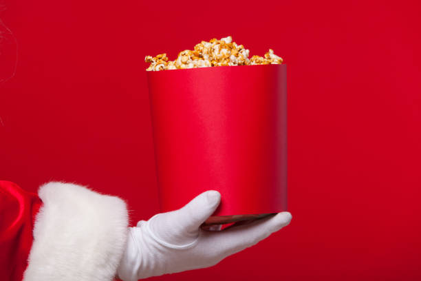 Christmas. Photo of Santa Claus gloved hand With a red bucket with popcorn, on a red background stock photo