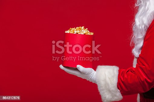 istock Christmas. Photo of Santa Claus gloved hand With a red bucket with popcorn, on a red background 864312876