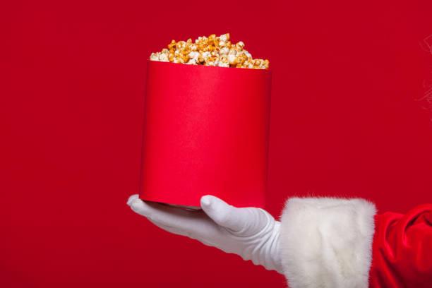 weihnachten. foto von santa claus behandschuhten hand mit einem roten eimer mit popcorn, auf rotem grund - kinder weihnachtsfilme stock-fotos und bilder