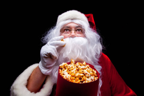 christmas. photo of santa claus gloved hand with a red bucket with popcorn, on a black background - christmas movie foto e immagini stock