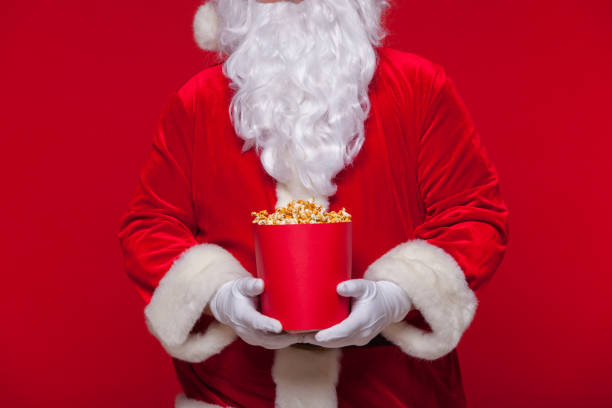 christmas. photo of santa claus gloved hand with a red bucket with popcorn, on a red background - christmas movie foto e immagini stock