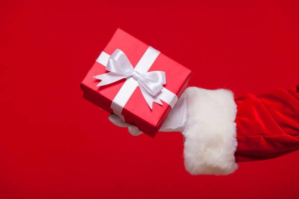 weihnachten foto von santa claus behandschuhten hand mit roten geschenkbox - besondere geschenke stock-fotos und bilder