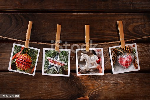 istock christmas photos hanging on rope against wooden background 529178253