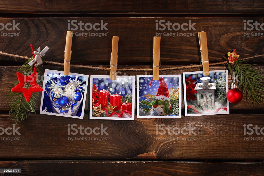 christmas photos hanging on rope against wooden background stock photo