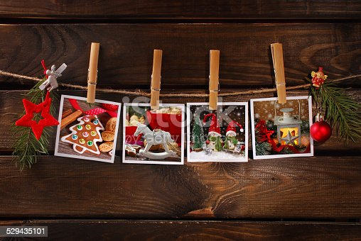 istock christmas photos hanging on rope against wooden background 529435101
