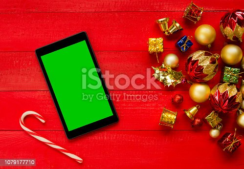 Christmas background with digital tablet on red wooden