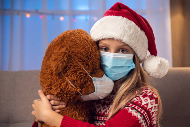 Christmas Little girl and Teddy Bear wearing Santa's hat and surgical mask. Coronavirus quarantine concept. christmas teddy bear stock pictures, royalty-free photos & images