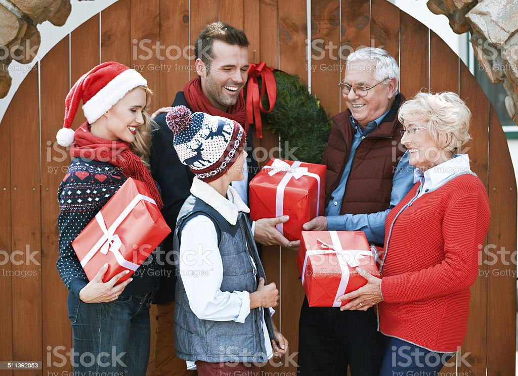 Christmas Mother, father and son visiting grandparents for Christmas, exchanging christmas gifts. Active Seniors Stock Photo