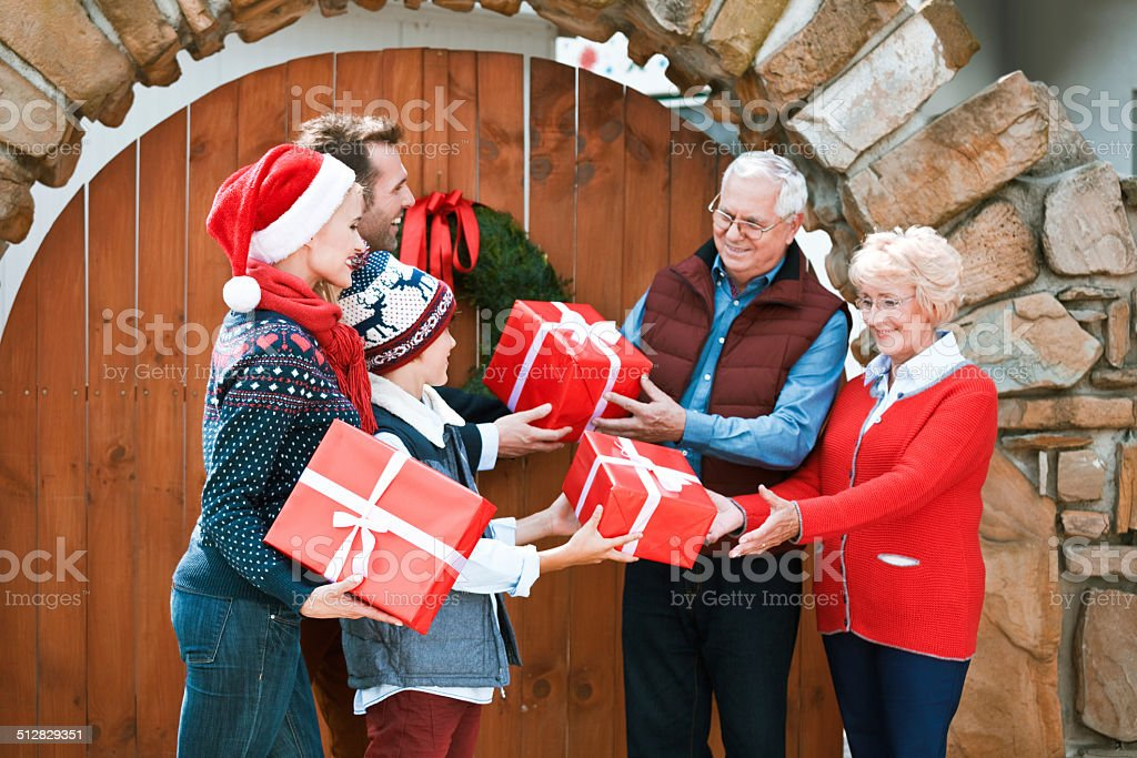 Christmas Mother, father and son visiting grandparents for Christmas, standing in front of entrance door and exchanging christmas gifts. Active Seniors Stock Photo