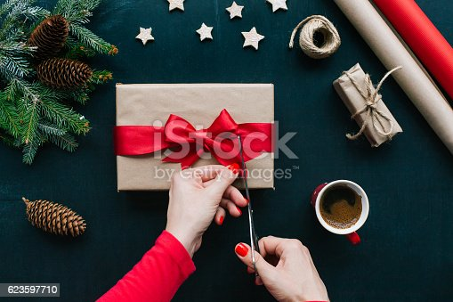 Concept of Christmas items on a table. Woman's hands wrapping Christmas gift